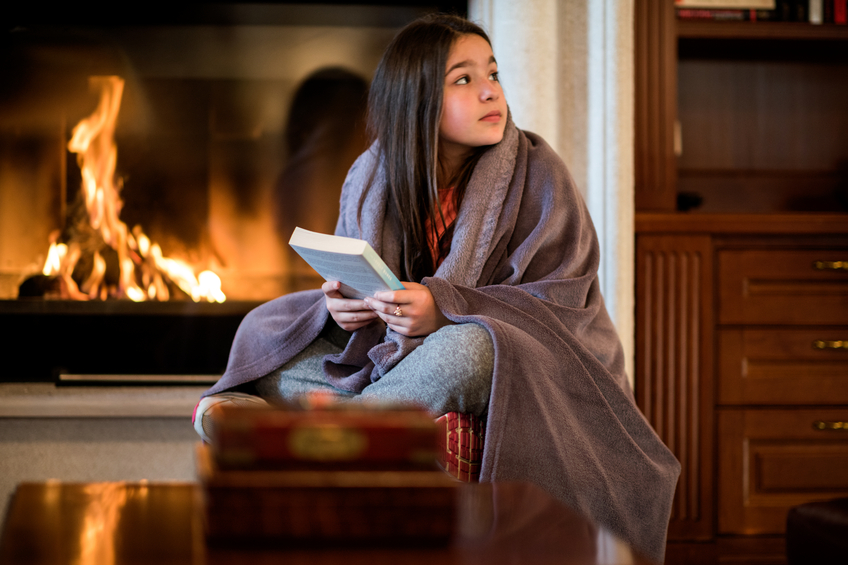 Girl holding a book by the fireplace