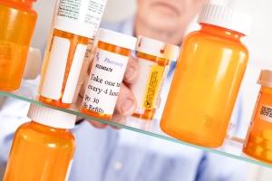 Man taking prescription pills out of medicine cabinet